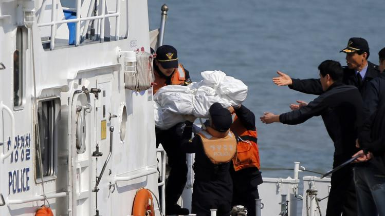 Body of missing passenger is carried to landing pier at a port in Jindo