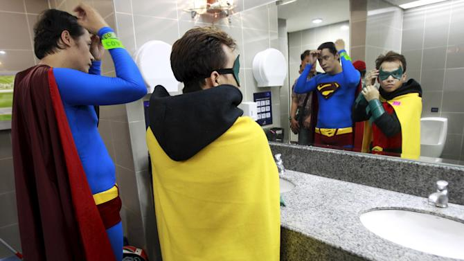 Participants wearing super heroes costume adjust their appearance at the mens room before joining the World DC Comics Super Heroes gathering in Manila