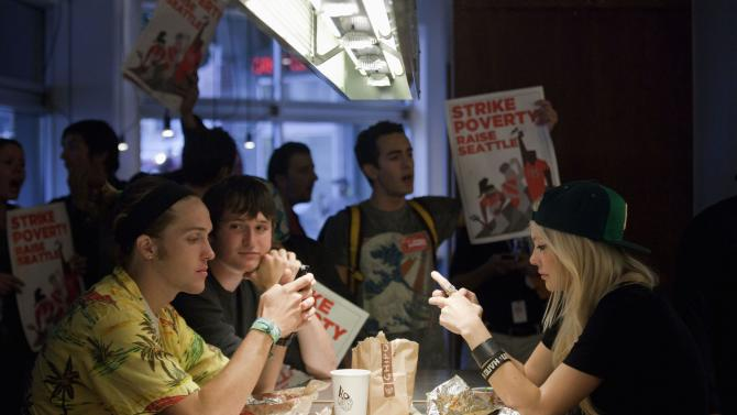 Patrons sit as their lunch is interrupted by demonstrators in Chipotle Mexican Grill during a strike aimed at the fast-food industry and the minimum wage in Seattle