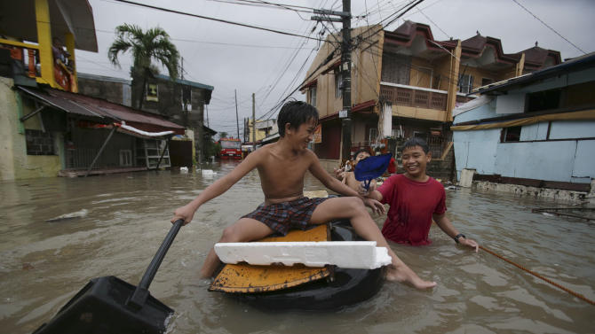 Filipino boys play along a flooded street in Las Pinas, south of Manila, Philippines on Monday, Aug. 19, 2013. Torrential rains brought the Philippine capital to a standstill Monday, submerging some areas in waist-deep floodwaters and making streets impassable to vehicles while thousands of people across coastal and mountainous northern regions fled to emergency shelters. (AP Photo/Aaron Favila)