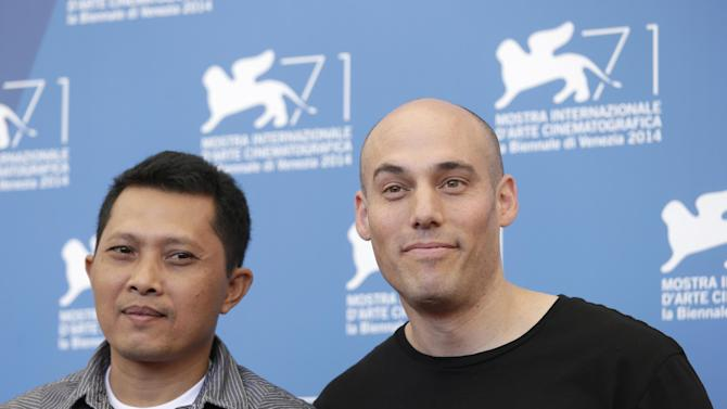 CORRECTS POSITION - Actor Adi Rukun, left, and director Joshua Oppenheimer pose for photographers at the photo call for the film The Look of Silence the 71st edition of the Venice Film Festival in Venice, Italy, Thursday, Aug. 28, 2014. (AP Photo/David Azia)