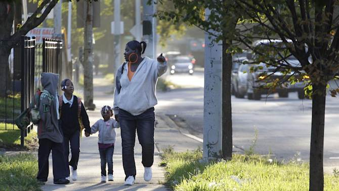 Leslie Sabbs-Kizer, right, walks her children  Nkai Melton, 8, Akaira Melton, 7, and Khaymya Smith, 3 to Bond Elementary school in Chicago, Wednesday morning, Sept. 19, 2012, after Chicago teachers voted to suspend their first strike in 25 years. Union delegates voted overwhelmingly Tuesday night to suspend the walkout after discussing a proposed contract settlement with the nation's third largest school district.  (AP Photo/M. Spencer Green)