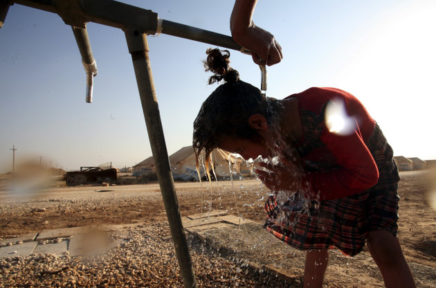 In this Thursday Aug. 2, 2012 photo a Syrian refugee girl washes up and cools off in Zaatari Refugee camp, in Mafraq, Jordan. Jordan is host to the largest number of Syrian refugees at 142,000, includ