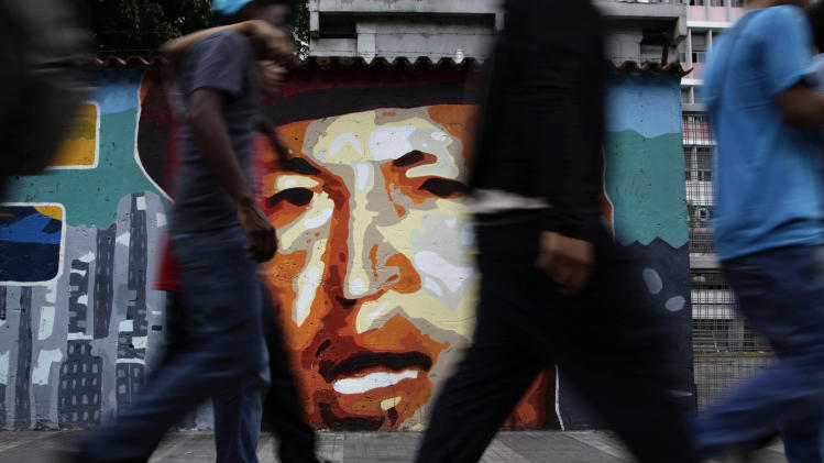 People walk by a mural of Venezuela's President Hugo Chavez in Caracas, Venezuela, Friday, April 20, 2012. Chavez is in Cuba to continue with cancer treatment. (AP Photo/Ariana Cubillos)