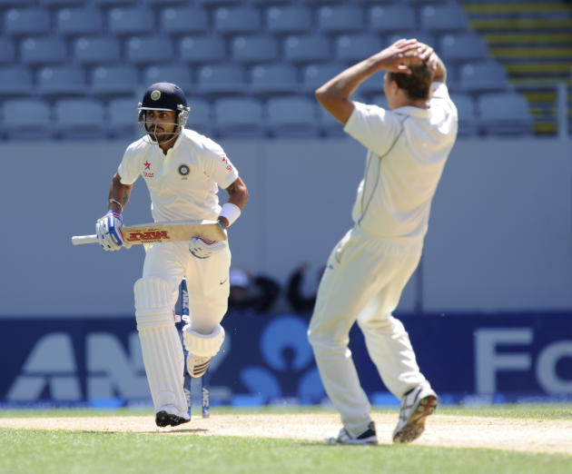 India's Virat Kohli, left, runs past against despairing New Zealand's Neil Wagner on the fourth day of the first cricket test at Eden Park in Auckland, New Zealand, Sunday, Feb. 9, 2014. (AP Photo/SNP