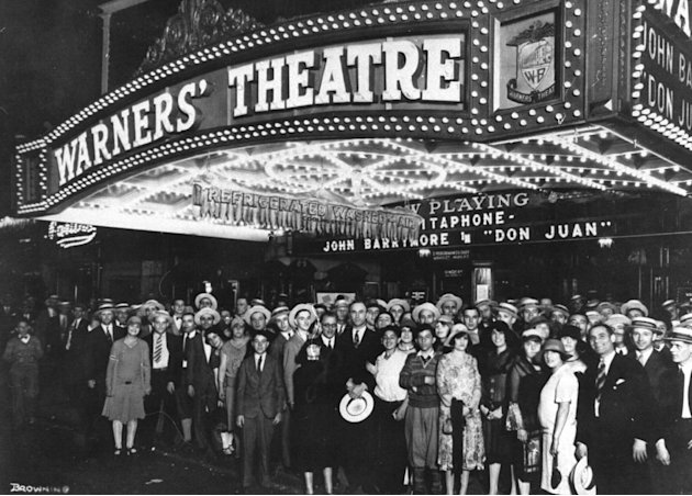 "This 1926 image shows crowds posing outside Warner's Theatre in New York for the 1926 opening of John Barrymore in ""Don Juan.""  This silent film's synchronized score led directly to the breakthrough t"