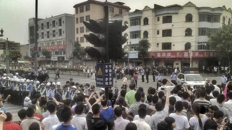Workers protest during a strike as police stand guard at a crossroads near the factory area of Yue Yuen Industrial, in Dongguan