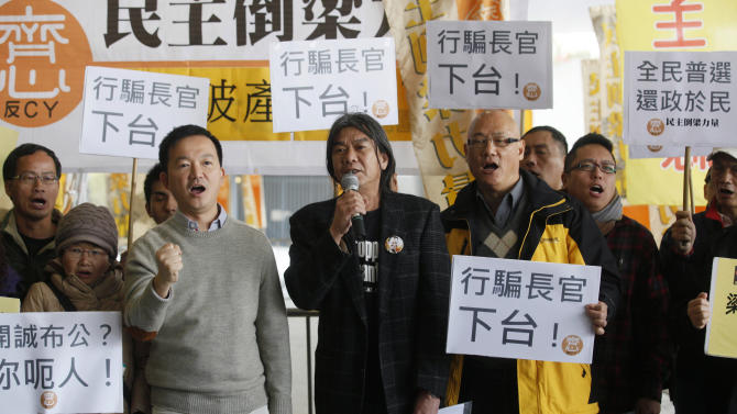 "Leung Kwok-hung, also known as Long Hair, a member of the Legislative Council, center, stands with other pro-democracy members of Hong Kong's legislature and other protesters as they display placards reading ""Chief Executive, step down"" outside the Legislative Council in Hong Kong Wednesday, Jan. 9, 2013. Lawmakers were making a symbolic attempt Wednesday to impeach Hong Kong's Beijing-backed leader, the latest sign of the widening gulf between the semiautonomous southern Chinese city and its political masters in Beijing. (AP Photo/Kin Cheung)"