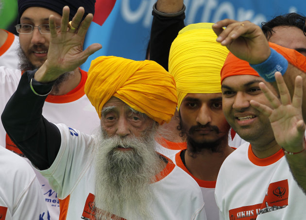 Centenarian marathon runner Fauja Singh, 101, left, originally from Beas Pind, in Jalandhar, India but who now lives in London, waves after finishing a 10-kilometer race, held as part of the annual Ho