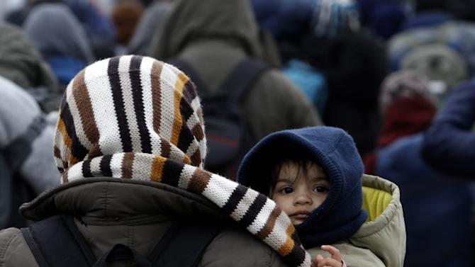 A baby looks back over woman's shoulder as they move with a group of refugees towards the border with Serbia, from the transit center for refugees near northern Macedonian village of Tabanovce, Wednesday, Feb. 10, 2016. Macedonian authorities are reinforcing a barrier at the country's border with Greece that is designed to limit the number of migrants crossing into the country, accepting people only from war-affected zones who declare Austria or Germany as their final destination. (AP Photo/Boris Grdanoski)