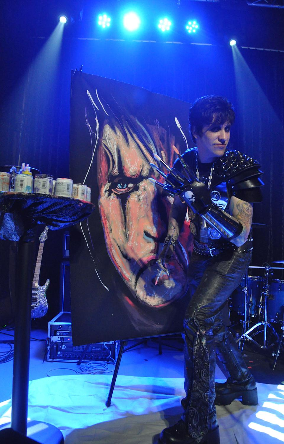 Speed painter Rock Demarco crafts a giant portrait of Alice Cooper ahead of an all-star concert benefiting the Brennan Rock & Roll Academy, Thursday, March 28, 2013, in Sioux Falls, S.D. (AP Photo/Dirk Lammers)