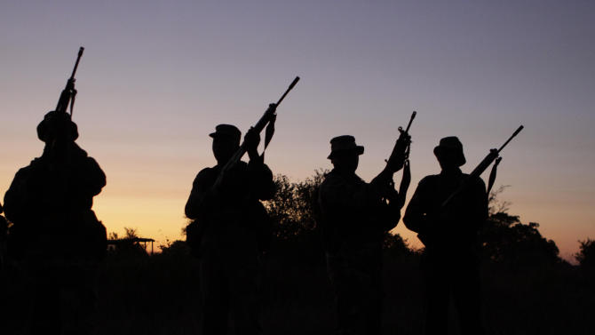 In this photograph taken Tuesday July 19, 2011 armed soldiers stage a night patrol at an isolated outpost in the Kruger National Park's Sabi River valley, close to the Mozambican border, for visiting press.  Armed soldiers, park officials, judicial, customs and tax officers are coordinating a multi-pronged strategy in a bid to end rhino poaching in the country's flagship park. (AP Photo/Denis Farrell)