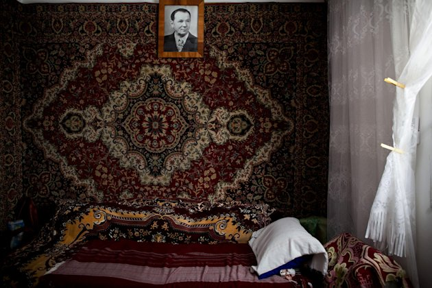In this Oct. 30, 2012 photo, a carpet covers the bedroom wall in Tsila Gorenstein's apartment in Be'er Sheva, southern Israel. In her native Moldova, heavy carpets were hung on the walls to heat homes