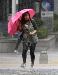 A woman walks in the strong wind and rain caused by Typhoon Sanba in Seoul, South Korea, Monday, Sept. 17, 2012. (AP Photo/Lee Jin-man)