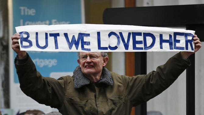 A man holds up a banner before former British Prime Minister Margaret Thatcher's ceremonial funeral procession in London, Wednesday, April 17, 2013. The Iron Lady is being laid to rest — yet even in death, she remains a polarizing figure. World leaders and dignitaries from 170 countries are due to attend the funeral of former British Prime Minister Margaret Thatcher on Wednesday, an elaborate affair with full military honors that will culminate in a service at St. Paul's Cathedral in London. (AP Photo/Matt Dunham, Pool)