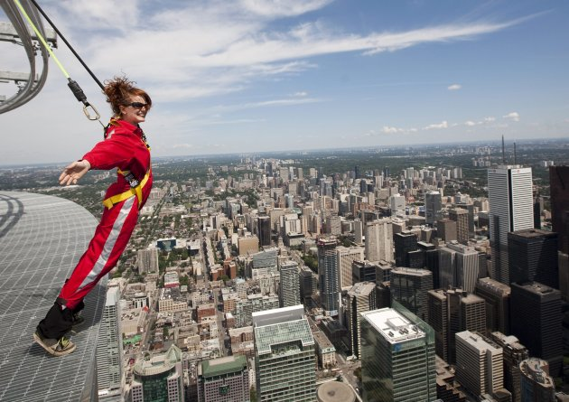 Canadian Press reporter Alex Posadzki leans over Toronto's downtown while participating in a media preview of EdgeWalk on the CN Tower on Wednesday, July 27, 2011.   (AP Photo/The Canadian Press, Darr