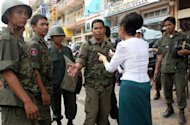Kek Galabru (2nd R-back to camera), president of LICADHO -- a Cambodian human rights NGO -- seen here speaking to policemen in Phnom Penh, in 2006, as rights activists marked the first anniversary of the trial of two men convicted of killing popular union leader Chea Vichea