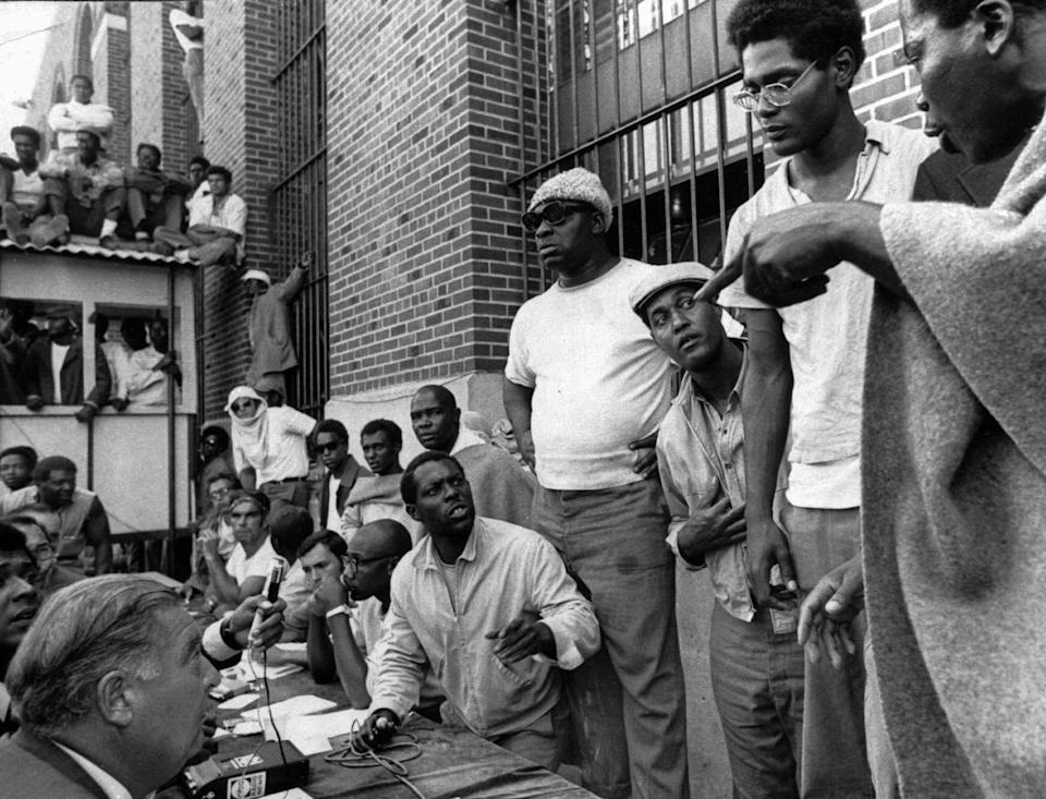 FILE - In this file photo of Sept. 10, 1971, inmates of Attica state prison, right, negotiate with state prisons Commissioner Russell Oswald, lower left, at the facility in Attica, N.Y., where inmates had taken control of the maximum-security prison in rural western New York. New York's Attorney General Eric Schneiderman has asked a state judge to unseal documents about the 1971 riot and retaking of Attica state prison in the nation's bloodiest prison rebellion. (AP Photo, File)