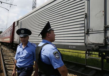 Ukrainian police stand guard near a train carrying the remains of victims of Malaysia Airlines MH17 downed over rebel-held territory in eastern Ukraine after it arrived in the city of Kharkiv, eastern Ukraine