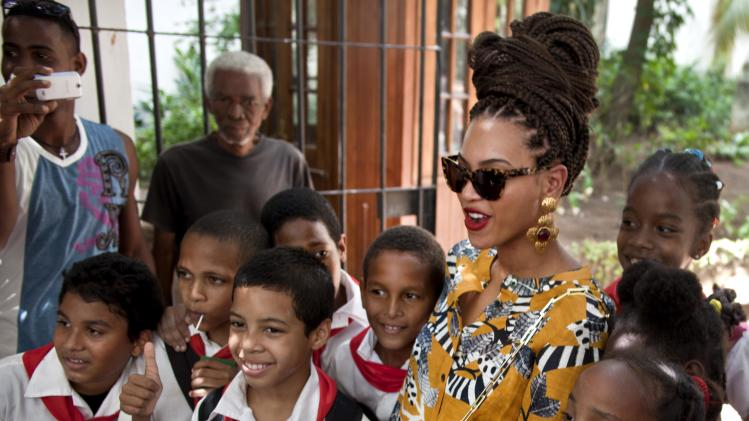 U.S. singer Beyonce poses for photos with school children as she tours Old Havana, Cuba, Thursday, April 4, 2013. Beyonce is in Havana with her husband, rapper Jay-Z, on their fifth wedding anniversary. (AP Photo/Ramon Espinosa)