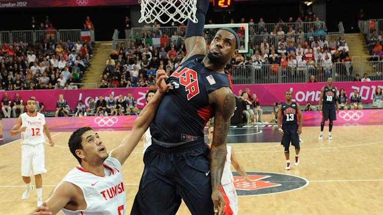 The United States' forward LeBron James scores next to Tunisian forward Mohamed Hadidane during their men's preliminary round group A basketball match at the 2012 Summer Olympics on Tuesday, July 31, 2012, in London. (AP Photo/Mark Ralston, Pool)