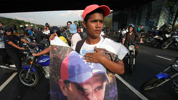 A demonstrator holds a poster of opposition presidential candidate Henrique Capriles as  as other Capriles supporters and students block a highway in the Altamira neighborhood in Caracas, Venezuela, Monday, April 15, 2013. National Guard troops fired tear gas and plastic bullets to disperse students protesting the official results in Venezuela's disputed presidential election.(AP Photo/Fernando Llano)