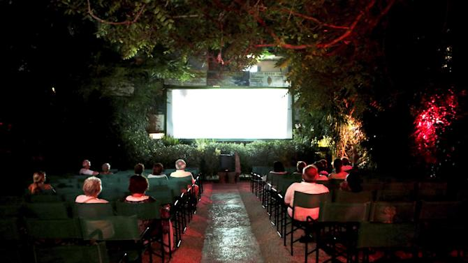 "Greek spectators at the open air cinema ""Oasis"" in Athens on August 1, 2014"