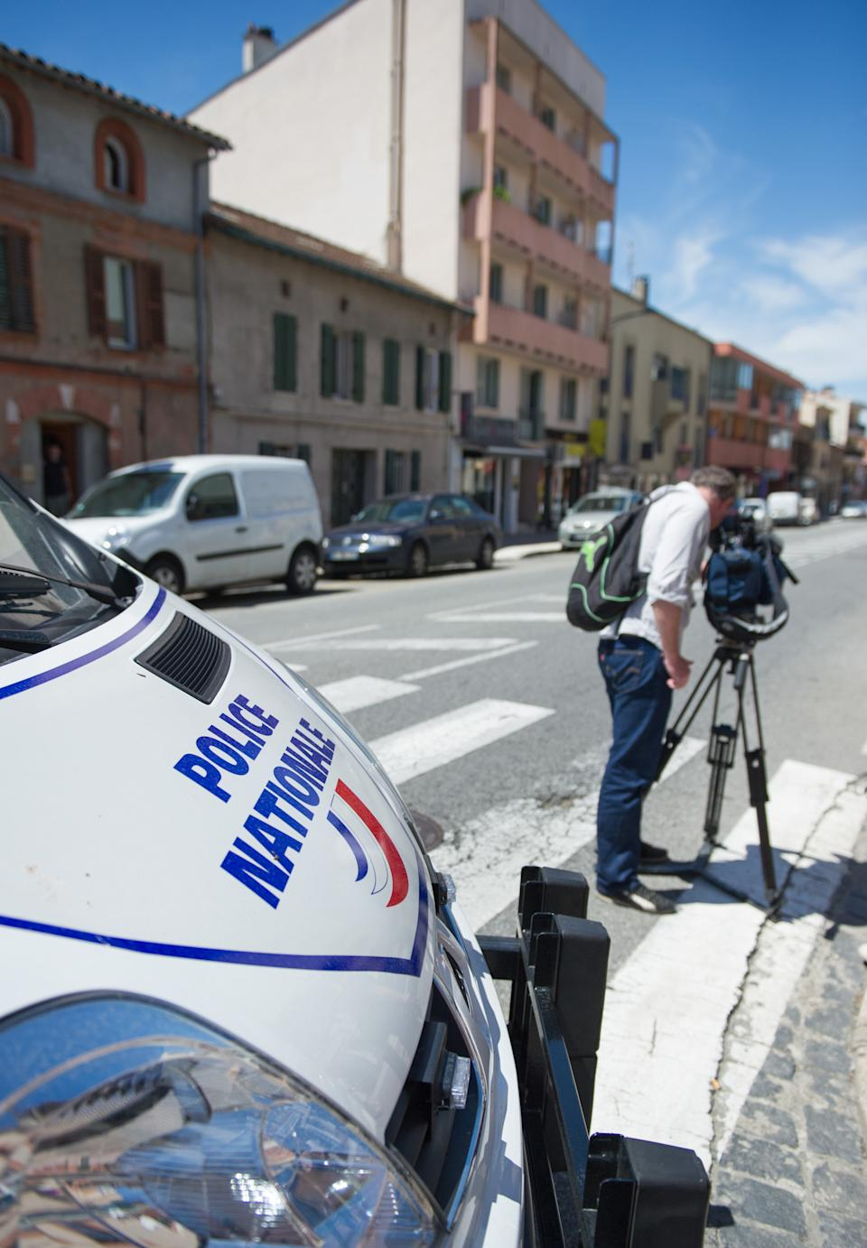 A  police van parks near a cameraman near where a man took hostages in a bank in the southern French city of Toulouse and fired a shot, police said, Wednesday, June 20, 2012. French television reported that he claimed allegiance to the al-Qaida terrorist group.(AP Photo/Bruno Martin)