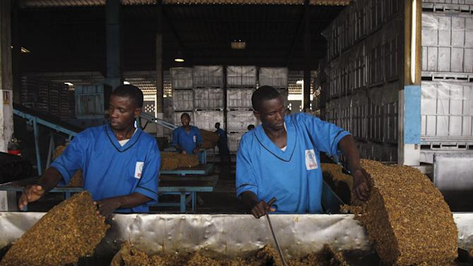 Men work at a rubber factory in Songon village