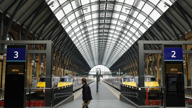 A man walks along an empty platform at King's Cross Station in London