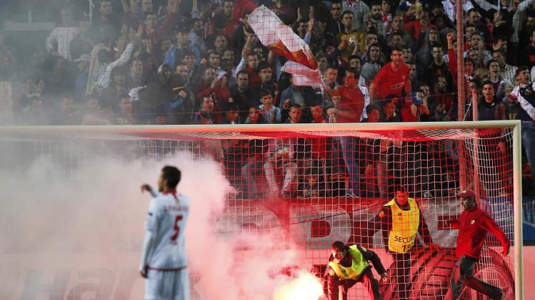 Security personnel remove a flare from the pitch during the Europa League soccer match between Sevilla and Real Betis in Seville