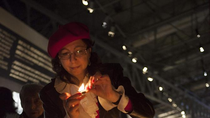 A woman lights a candle during a ceremony marking International Holocaust Remembrance Day in Russia's first Jewish Museum in Moscow, Russia, Sunday, Jan. 27, 2013. (AP Photo/Alexander Zemlianichenko Jr)
