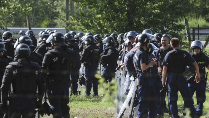 Hungarian riot police stand next to migrant reception centre in Roszke