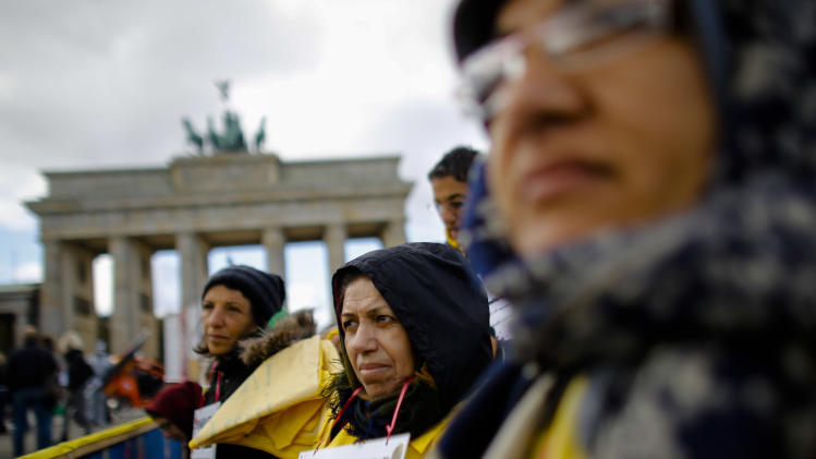 Supporters of the National Council of Resistance of Iran attend a hunger strike in protest against the situation in the Ashraf and Liberty Camps near Baghdad, in front of the Brandenburg Gate in Berlin, Germany Friday, Oct. 18, 2013. (AP Photo/Markus Schreiber)