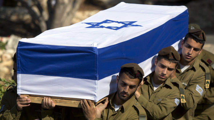 Israeli soldiers carry the coffin of Staff Sgt. Moshe Melako, 20, during his funeral at the Mount Herzel military cemetery in Jerusalem, Monday, July 21, 2014. Melako was one of 13 soldiers killed in several separate incidents in Shijaiyah on Sunday, as Israel-Hamas fighting exacted a steep price, killing scores of Palestinians and more than a dozen Israeli soldiers. In Israel, a country where military service is mandatory for most citizens, military losses are considered every bit as tragic as civilian ones. (AP Photo/Sebastian Scheiner)