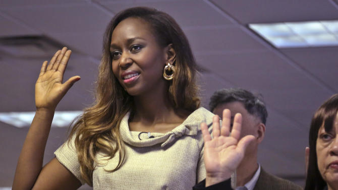 """Immaculee Ilibagiza raises her right hand along with 50 new citizens as she says the oath of citizenship, during a naturalization ceremony at the U.S. Citizenship and Immigration Services  on Wednesday, April 17, 2013, in New York.  """"Who would know that this fantasy would finally happen,"""" said Ilibagiza, author of the best seller """"Left to Tell, Discovering God Amidst the Rwandan Holocaust.""""  She sought asylum in the U.S. after fleeing the 1994 Rwandan genocide, which claimed more than 500,000 lives.  (AP Photo/Bebeto Matthews)"""
