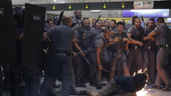 Riot police and security officers clash with a demonstrator (bottom) inside Faria Lima subway station during a protest against fare hikes for city buses, subway and trains in Sao Paulo