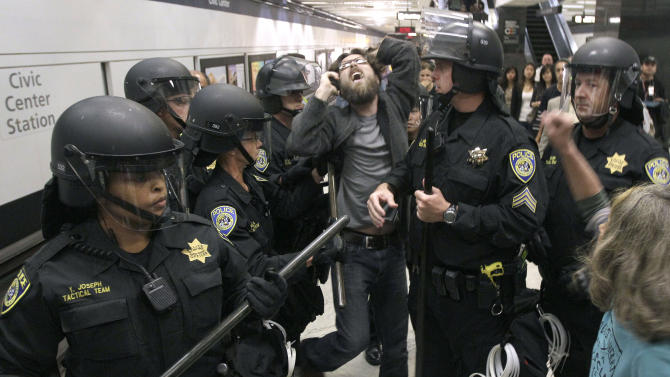 BART police officers push back a protester at the Civic Center station in San Francisco, Monday, Aug. 15, 2011. Cellphone service was operating as protesters gathered at a San Francisco subway station during rush-hour several days after transit officials shut wireless service to head off another demonstration. (AP Photo/Jeff Chiu)