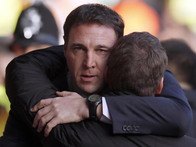 Cardiff City's manager Mackay embraces Liverpool's manager Rodgers as he walks onto the pitch before their English Premier League soccer match at Anfield in Liverpool