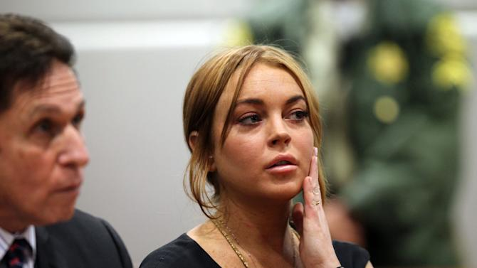 FILE - In this Jan. 30, 2013 file photo, actress Lindsay Lohan appears in Los Angeles court with her new attorney Mark Heller, left, for a pretrial hearing, in a case filed over the actress' June 2012 car crash. Lohan is due back in court on Monday, March 18, 2013, for a hearing that will lay out when her trial will begin on misdemeanor charges she lied to police and was driving recklessly when her sports car crashed in June. Lohan's trial is scheduled to begin this week, but her attorney has previously sought a delay. (AP Photo/David McNew, Pool, File)