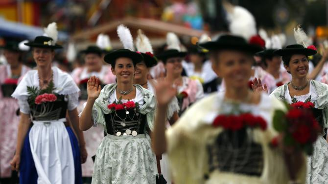 People in traditional Bavarian clothes take part in the Oktoberfest parade in Munich