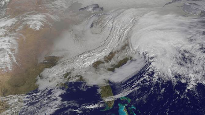 This image released by NASA from NOAA's GOES-13 satellite captured at 9:01 a.m. on Friday, Feb. 8, 2013 shows a massive winter storm coming together as two low pressure systems merge over the northeast U.S. Snow began falling across the Northeast on Friday, ushering in what was predicted to be a huge, possibly historic blizzard and sending residents scurrying to stock up on food and gas up their cars. (AP Photo/NASA)