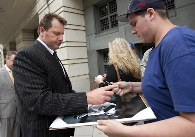 Former Major League Baseball pitcher Roger Clemens, left, signs autographs as he leave federal court in Washington, Monday, June 5, 2012, after court ended for the day in his perjury trial.  (AP Photo