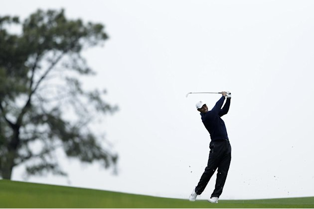 Tiger Woods hits his second shot on the 14th fairway of the north course at Torrey Pines Golf Course during the second round of the Farmers Insurance Open golf tournament Friday, Jan. 25, 2013, in San