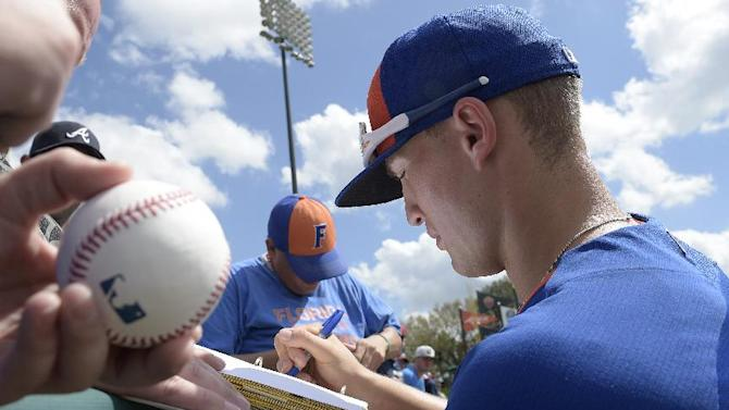 New York Mets' Brandon Nimmo, right, signs autographs for fans before a spring training baseball game against the Atlanta Braves Wednesday, March 4, 2015, in Kissimmee, Fla.(AP Photo/Phelan M. Ebenhack)