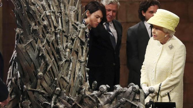 Britain's Queen Elizabeth looks at the Iron Throne as she visits the set of TV series Game of Thrones, in Belfast