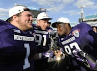 Northwestern defensive lineman Brian Arnfelt (91) and Bo Cisek (1) holds the trophy while their teammate Will Hampton (92) kisses it after the Gator Bowl NCAA college football game against Mississippi State, Tuesday, Jan. 1, 2013 in Jacksonville, Fla. Northwestern won 34-20. (AP Photo/Stephen Morton)
