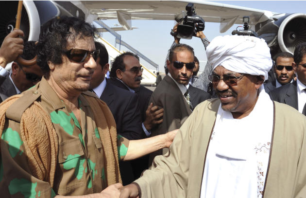 Sudanese president Omar al-Bashir, right, receives Libyan leader Muammar Gadhafi upon his arrival at the Khartoum International Airport in Khartoum, Sudan, Tuesday, Dec. 21, 2010. The leaders of Egypt