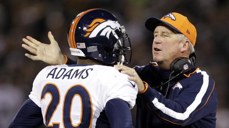 Denver Broncos head coach John Fox, right, talks with strong safety Mike Adams (20) during the second quarter of an NFL football game against the Oakland Raiders in Oakland, Calif., Thursday, Dec. 6, 2012. (AP Photo/Marcio Jose Sanchez)