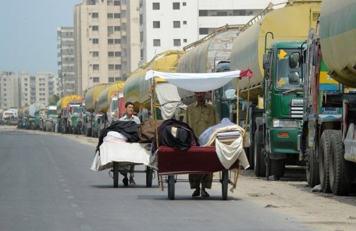 <p>Street vendors selling clothing material push their carts past oil tanker trucks parked on the side of a road in Karachi on July 12. Pakistan on Tuesday signed a deal with the United States governing arrangements for NATO convoys travelling to Afghanistan, seeking to draw a line under a seven-month border blockade.</p>